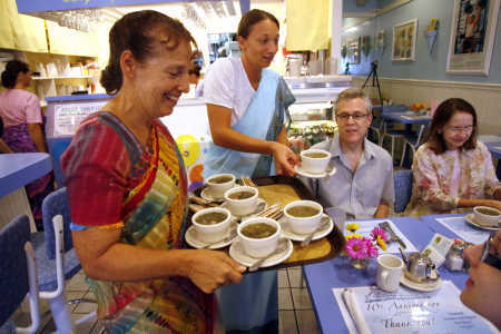 (PHOTO BY DOUGLAS R. CLIFFORD | TIMES) Drishti Pliske of Miami, left, and Kamila Hozlarova of Hudson serve spinach-artichoke soup to James Hughes of Oldsmar, Bonnie Starr of Largo and Betsie Hughes of Oldsmar, at lower right, during a 10th anniversary celebration dinner Sunday at Consciousness Blossoms, a vegetarian restaurant in Palm Harbor that shares a message of peace.